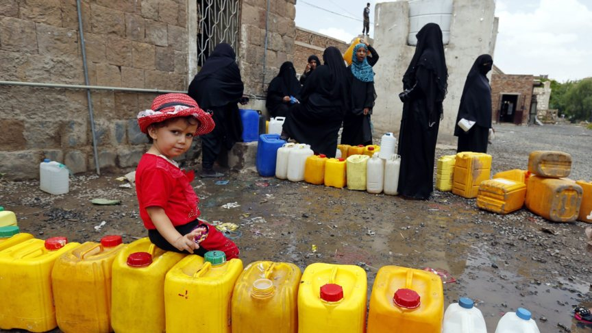 Yemenis stand in line for drinking water in between Saudi bombings