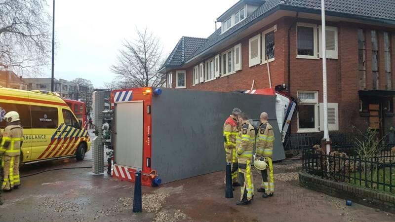 Tankwagen brandweer kantelt na botsing tegen woning.
