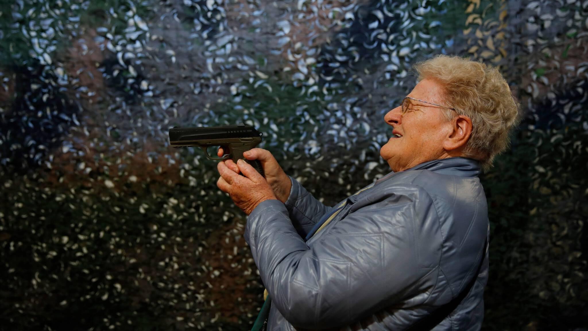 Een vrouw test een pistool op een wapenbeurs in het Zwitserse Luzern (Copyright AFP)