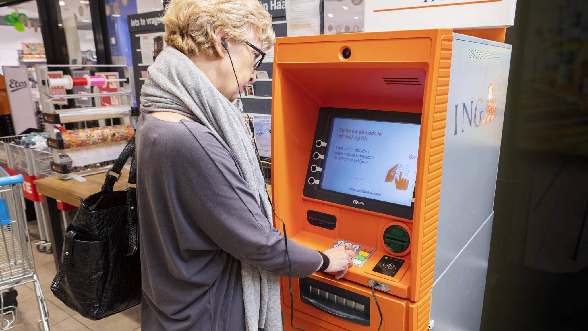 geldautomaat met vrouw die geld opneemt